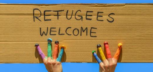 Refugees welcome - Hände mit bunten Fingern halten ein Pappschi